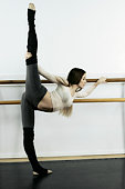 Ballet dancer stretching in dance studio.
