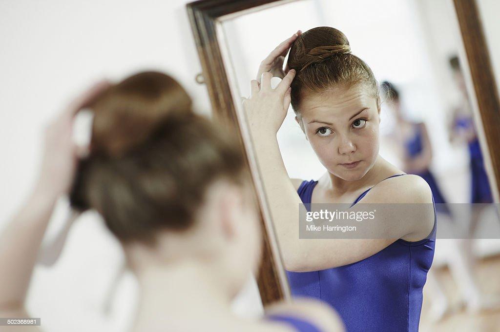 Ballet dancer tying hair in bun in mirror.
