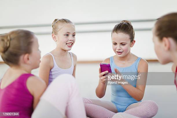 Ballet dancer using cell phone in studio