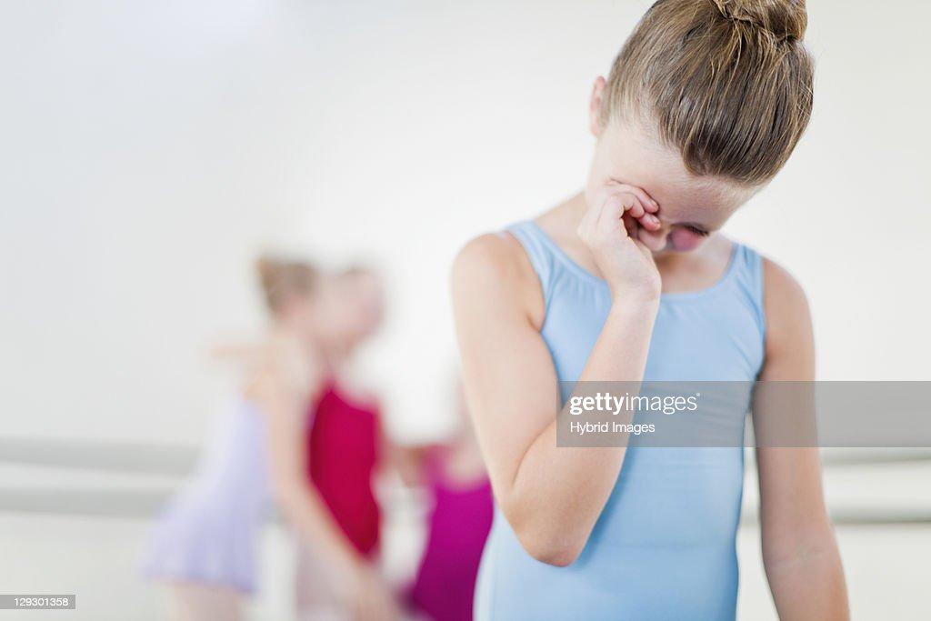 Ballet dancer wiping her eyes in studio : Stock Photo