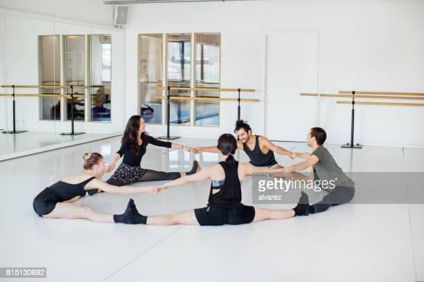 Bailarines de ballet haciendo estiramiento ejercen en círculo