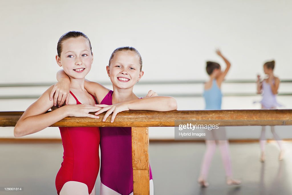 Ballet dancers embracing at barre : Stock Photo