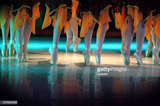 Ballet dancers feet wearing orange and black costume
