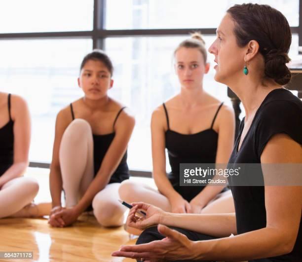 Ballet dancers listening to teacher in studio
