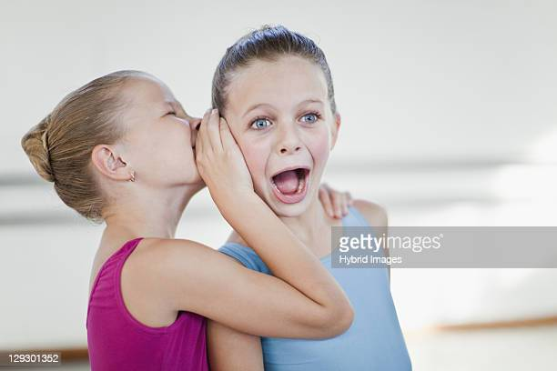 Ballet dancers whispering in studio