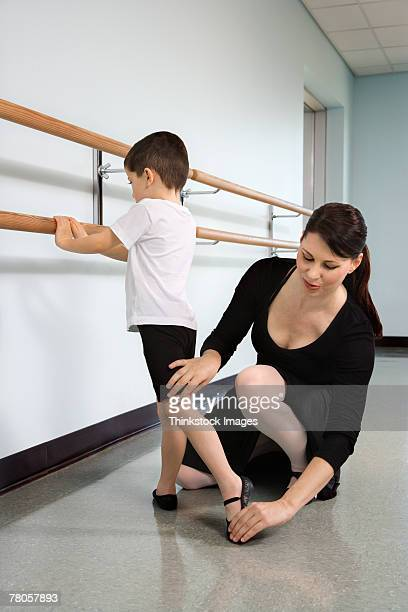 Ballet instructor correcting boy's position