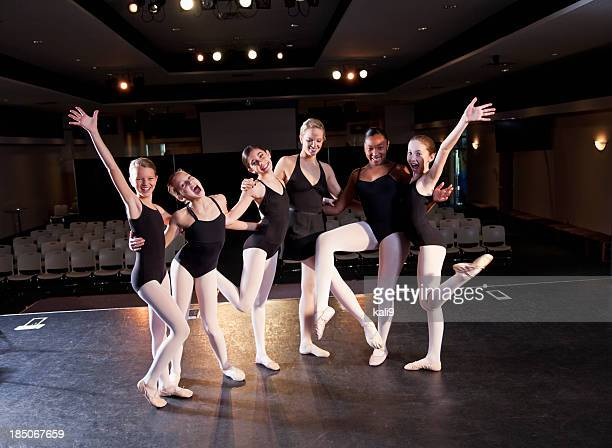 Ballet instructor with students on stage in auditorium