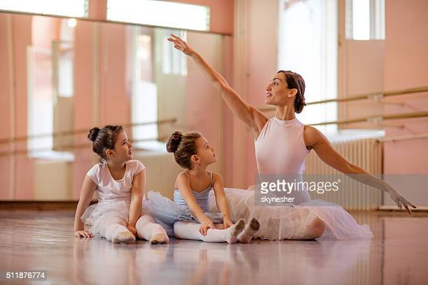 Ballet instructor with two little girls during ballet class.