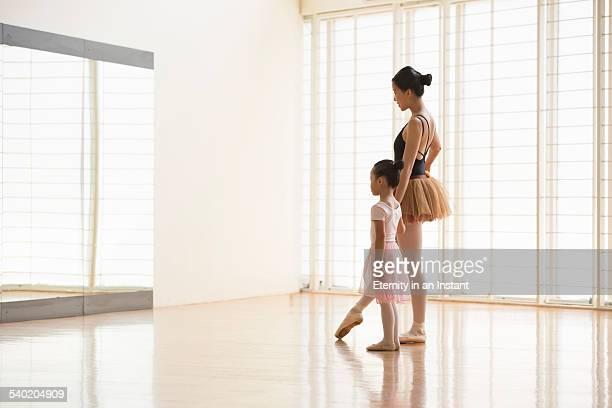 Ballet teacher and student practicing in studio,