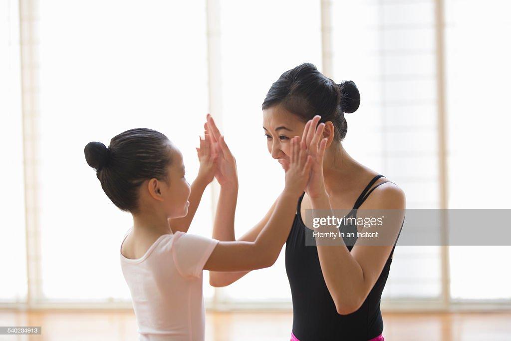 Ballet teacher congratulating young student.
