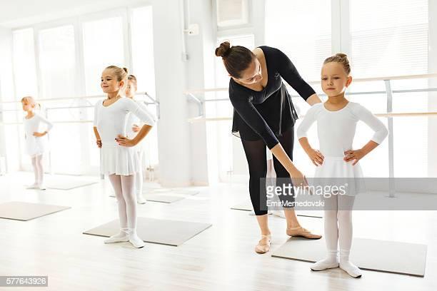 Ballet teacher helping girls with postures during ballet class.