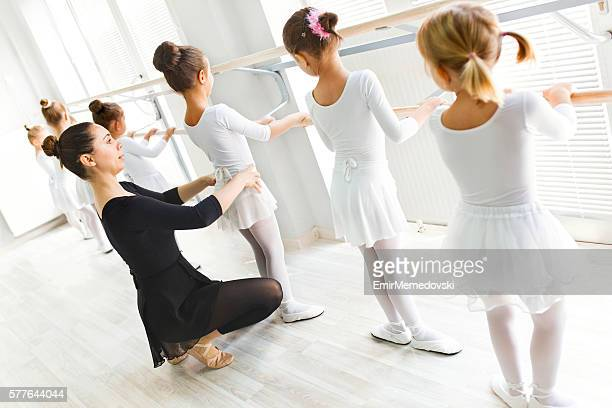 Ballet teacher helping girls with postures during ballet class.