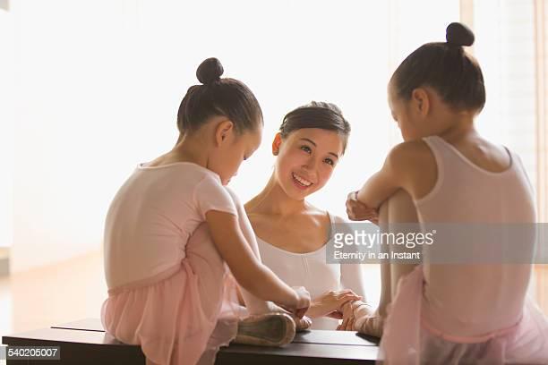 Ballet teacher helping young ballerinas