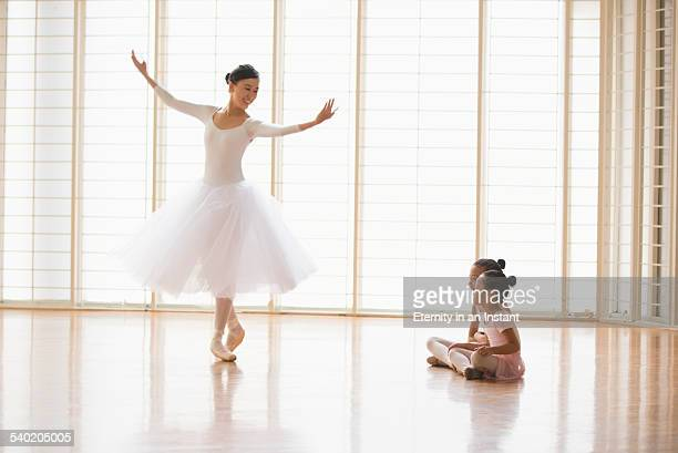 Ballet teacher showing young girls how to dance
