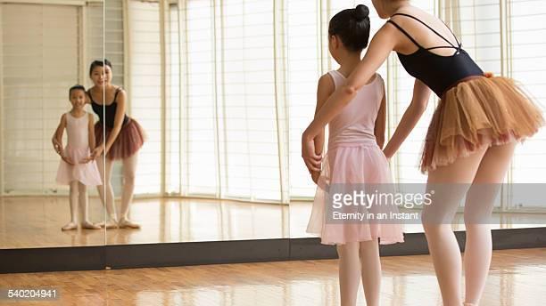 Ballet teacher teaching a young ballerina