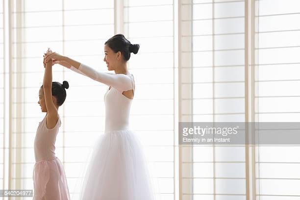 Ballet teacher teaching young ballerina.