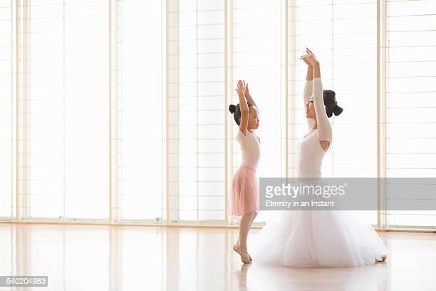 Ballet teacher teaching young ballerina