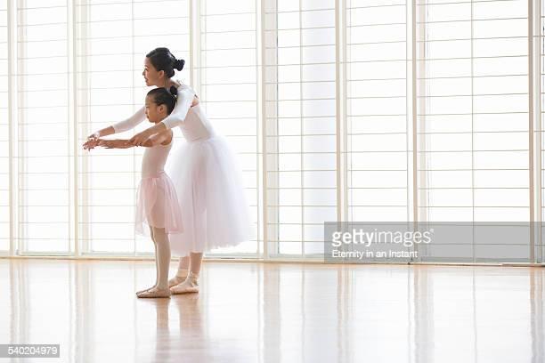 Ballet teacher teaching young ballerinas