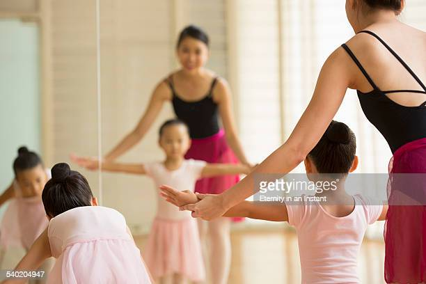 Ballet teacher teaching young students