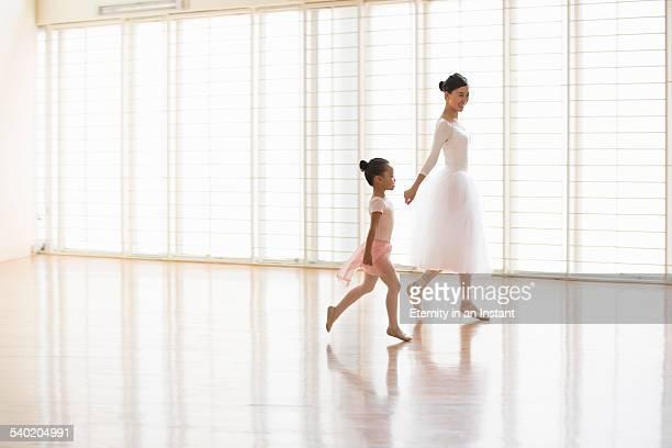 Ballet teaching a young ballerina in dance studio