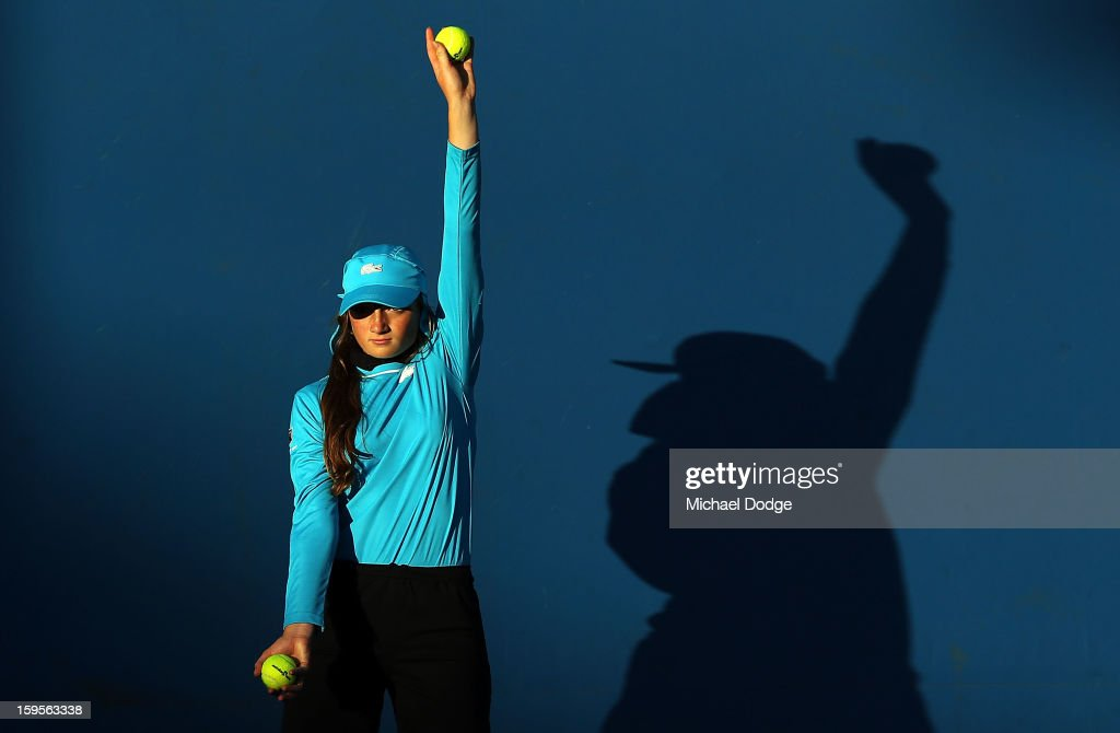 A ballgirl holds a ball up on an outside court late in the day during day three of the 2013 Australian Open at Melbourne Park on January 16, 2013 in Melbourne, Australia.
