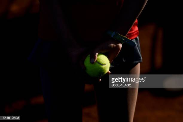 TOPSHOT A ballgirl holds a tennis ball during the ATP Barcelona Open 'Conde de Godo' tennis tournament in Barcelona on April 28 2017 / AFP PHOTO /...
