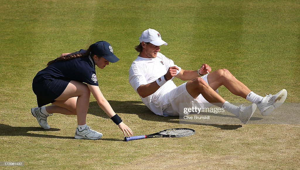 A ballgirl picks up Andreas Seppi of Italy's racquet after he slipped on the grass during the Gentlemen's Singles fourth round match against Juan Martin Del Potro of Argentina on day seven of the Wimbledon Lawn Tennis Championships at the All England Lawn Tennis and Croquet Club on July 1, 2013 in London, England.