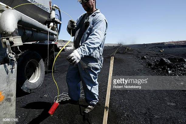 A ballistics technician lowers a blasting charge and yellow detonator cord into one of a string of holes in a coal seam at the Buckskin Coal Mine 12...