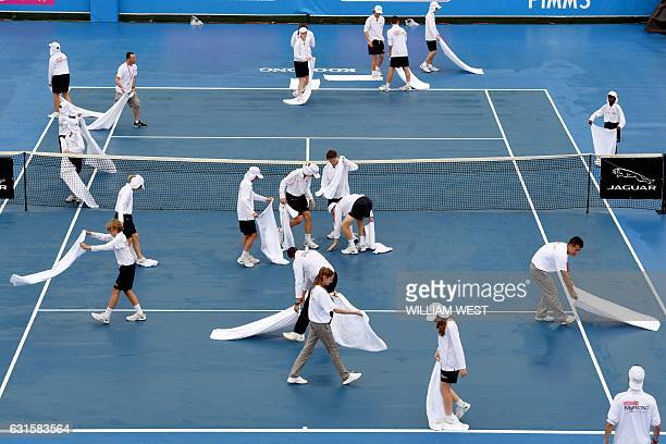 TOPSHOT Ballkids and ground staff attempt to dry the court as rain delays the final day of the Kooyong Classic tennis tournament in Melbourne on...