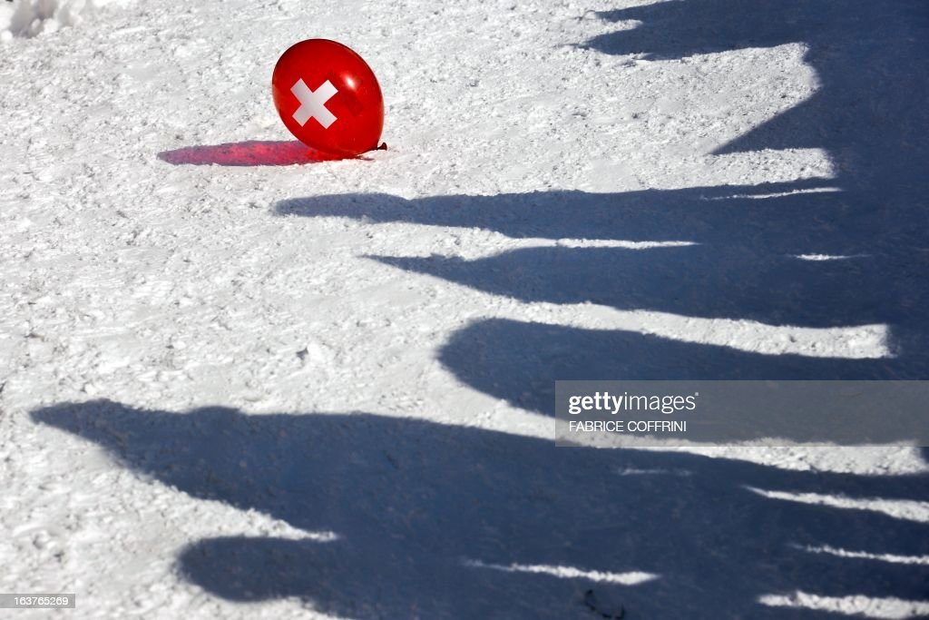 A ballon bearing the Swiss national flag with its white cross is seen laying on the snow near spectators' shadows during the Nation team event at the Alpine ski World Cup finals on March 14, 2013 in Lenzerheide. Germany won the event.