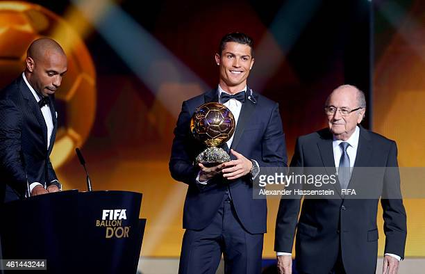 Ballon d'Or winner Cristiano Ronaldo of Portugal and Real Madrid accepts his award from Thierry Henry and FIFA President Joseph S Blatter during the...