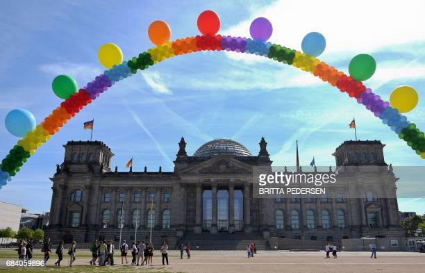 A balloon chain in rainbow colors is seen in front of the Reichstag building housing the German parliament as activists of the LGBT movementon...