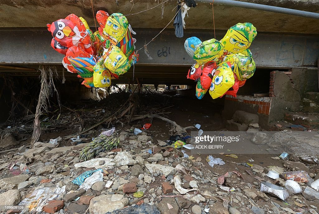 Balloon for sale hang next to the Ciliwung river following heavy floods in Jakarta on January 23, 2013. A spokesman for Indonesian National Disaster Mitigation Agency (BNPB) said more than 30,000 people were still living as refugees on January 22, while 20 people were killed during the widespread flooding that hit Jakarta last week. AFP PHOTO / ADEK BERRY