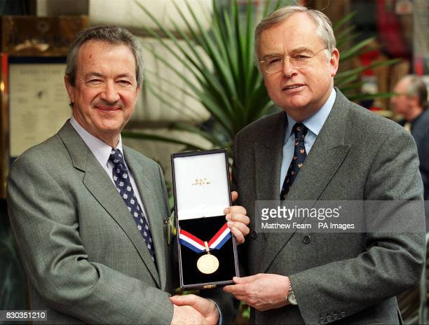 Balloonist Brian Jones from Bristol receives his ARP/O50 Golden Hero Award from BBC newsreader Martyn Lewis at the Cafe Royal in London
