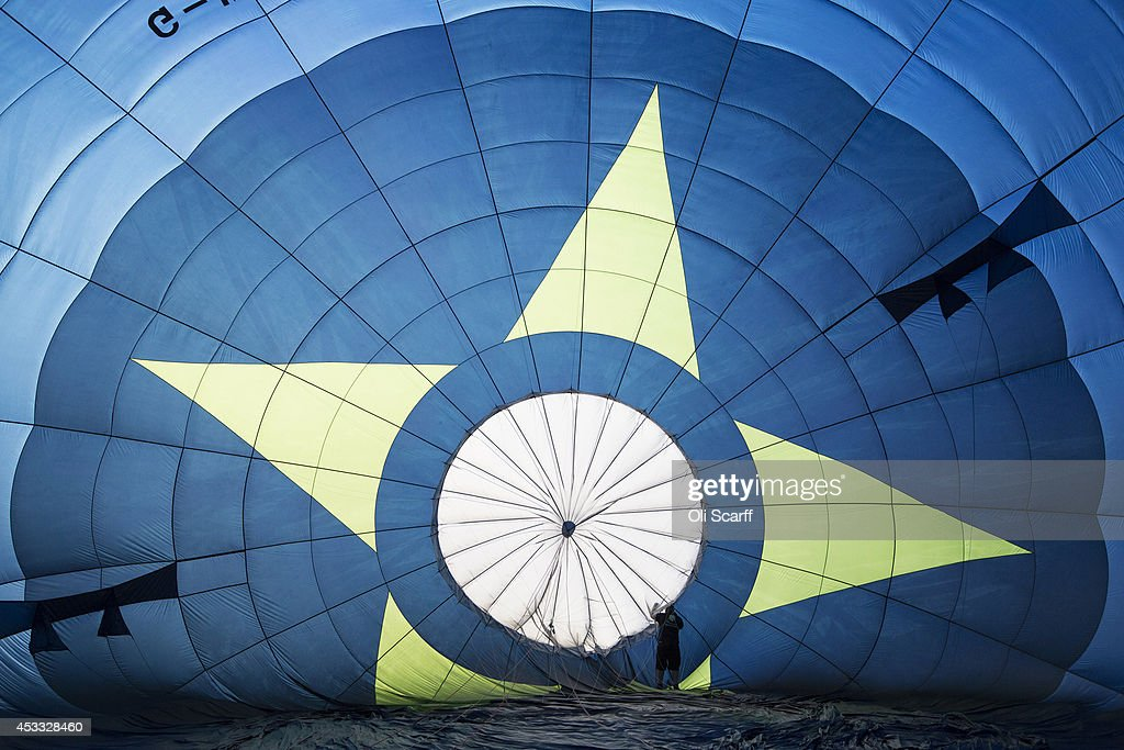 A balloonist prepares his hot air balloon in Aston Court for a mass ascent on the first full day of the Bristol International Balloon Fiesta on...