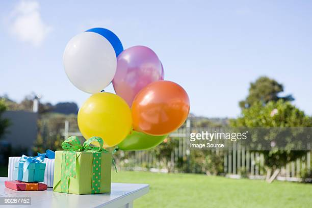 Balloons and birthday presents on table in garden