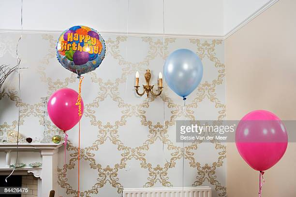 Balloons are floating in room.