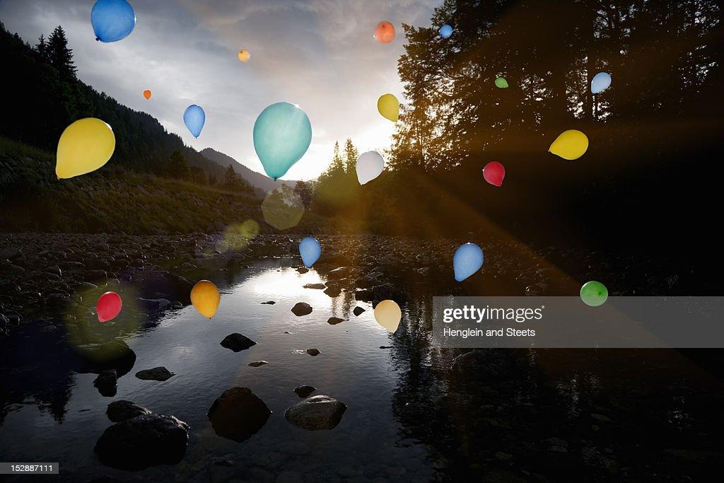 Balloons floating over still rocky lake