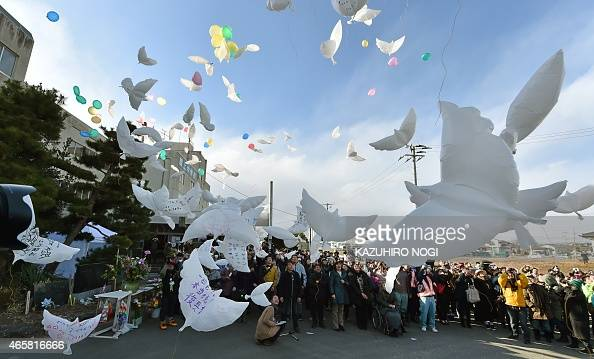 Balloons in the shape of doves are released into the air during a memorial service for victims of the 2011 quaketsunami disaster at the former...