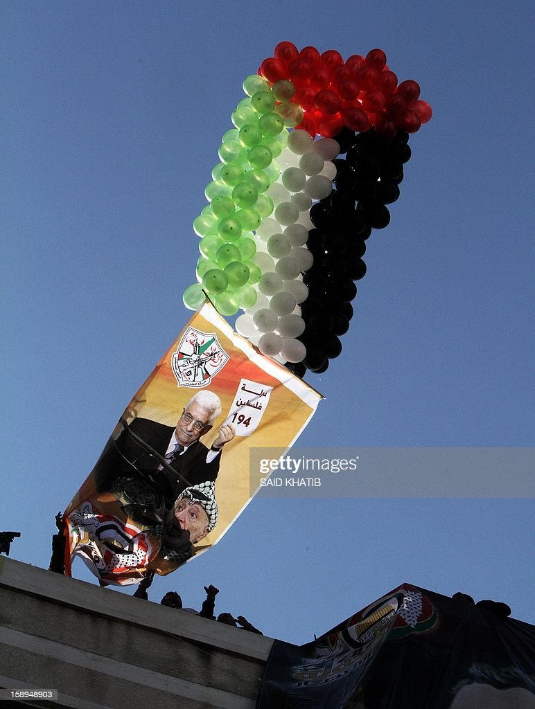 Balloons lift up a giant poster featuring Palestinian President Mahmoud Abbas and late Palestinian leader Yasser Arafat on January 4, 2013 during the Fatah's first mass rally in Gaza since Hamas seized control of the territory in 2007. Hamas, in a sign of reconciliation with Fatah, permitted the rally to go ahead as the climax of a week of Gaza festivities celebrating the 48th anniversary of Fatah taking up arms against Israel. AFP PHOTO / SAID KHATIB