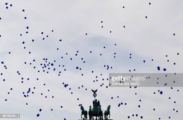 TOPSHOT Balloons pass the Brandenburg gate during the 'March For Europe' demonstration in Berlin on March 25 2017 to mark the 60th anniversary of the...