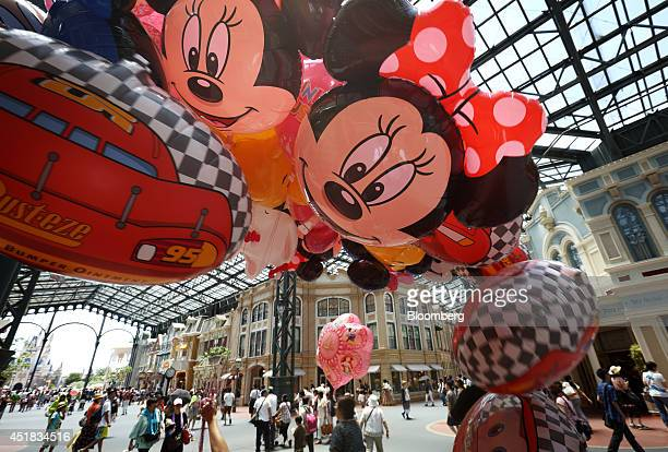 Balloons showing the Walt Disney Co characters Mickey Mouse center and Minnie Mouse right are held for sale by a cast member at Tokyo Disneyland...