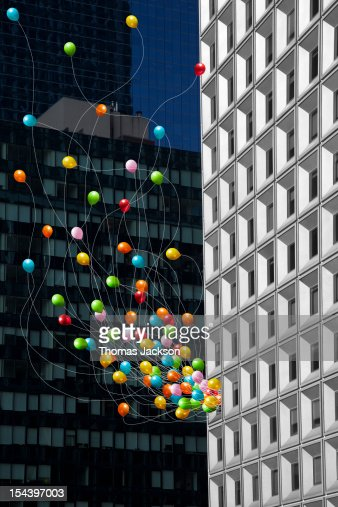 Balloons streaming from office building window