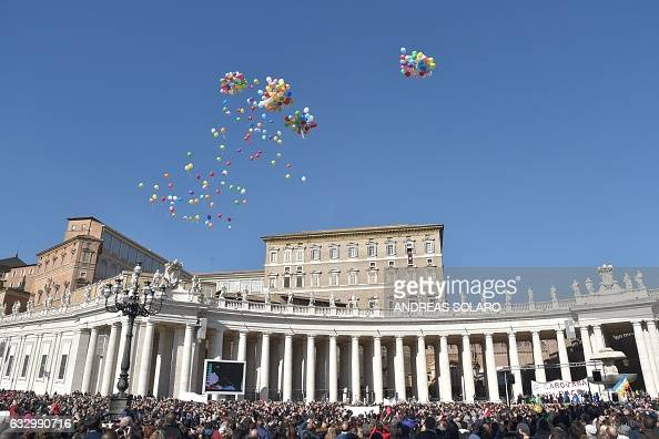 Balloons symbolising Peace are released at St Peter's square as Pope Francis stands with children at the window of the apostolic palace during the...