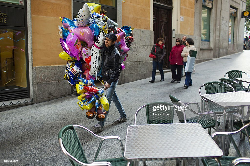 A balloon-seller walks past empty chairs outside a cafe in central Madrid, Spain, on Saturday, Dec. 29, 2012. Spain's economic activity kept falling in the fourth quarter, Bank of Spain says. Photographer: Angel Navarrete/Bloomberg via Getty Images