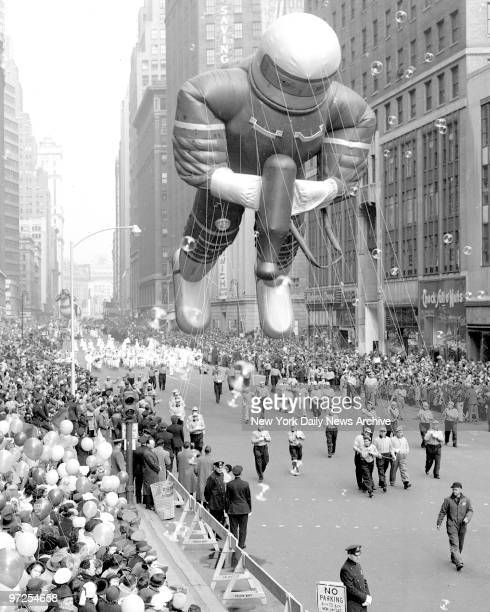 Balloonwaving crowds line Broadway at 34th Street as gigantic spaceman nears the end of his downtown journey in Macy's Thanksgiving Day parade Police...