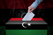 A hand casting a vote in a ballot box for an election in the Libya