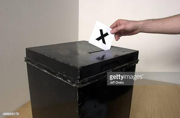 Ballot box Man casting ballot into ballot box whilst voting in election vote