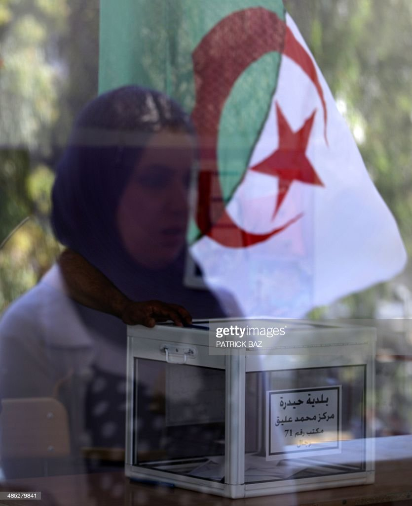 A ballot box sits on a table as a veiled woman and the Algerian national flag are reflected on the window of a classroom turned into a polling station for the presidential elections on April 17, 2014 in Algiers. Algeria's incumbent Presisdent Abdelaziz Bouteflika is widely expected to win despite his chronic health problems, warnings of fraud and opposition calls for a boycott.