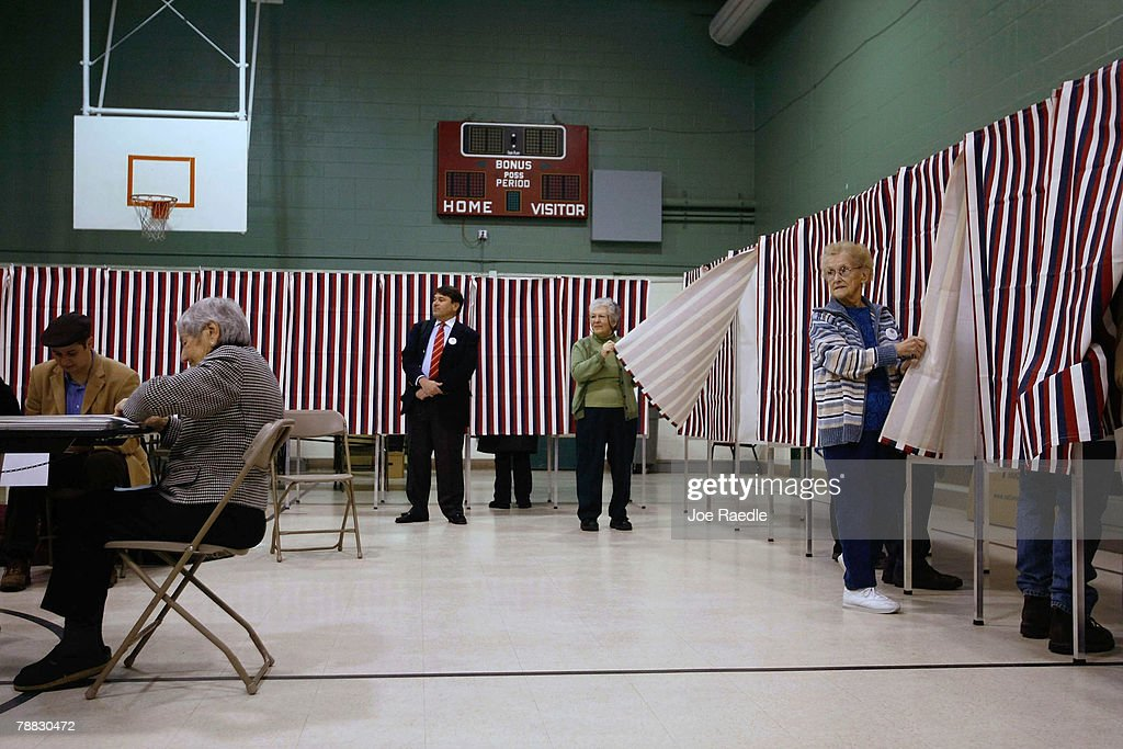 Ballot Inspectors Louise Rukey and Rita Paris hold the curtains open for voters to enter the voting booth as people vote at the Parker Varney School...
